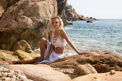 Sexy lady in white lace dress on rocky beach Stock Photography