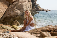 Sexy lady in white lace dress on rocky beach Royalty Free Stock Photos