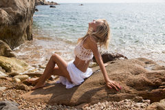 Sexy lady in white lace dress on rocky beach Royalty Free Stock Image