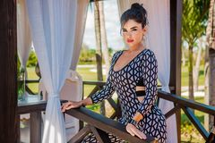 Sexy latina with long black hair in tight jumpsuit. Sexy latina with long black hair in park and restourant Royalty Free Stock Photos
