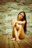 Sexy latina model sitting naked on wooden floor. Facing camera with legs and arms crossed covering up artistically in front of grey brick wall Stock Image