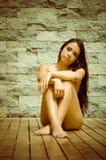 Sexy Latina-Modellsitzen nackt auf Bretterboden Stockbild
