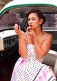 Sexy Latina Pinup Girl Putting on Lipstick Royalty Free Stock Photography