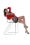 Sexy Latina Reclining. Pretty young Mexican woman in a red wrap, black and white striped mini dress with pearls around her wrist and reclined on a chair Royalty Free Stock Photo