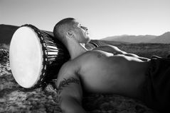 Sexy Latino resting. Muscular sexy Latino man laying on his back, high up on a cliff with his head resting on a drum. Looking in to the distance Royalty Free Stock Images