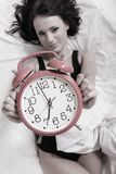 Sexy lazy girl lying with alarm clock on bed Stock Photo