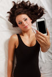 Sexy lazy girl lying with phone on bed in bedroom Stock Photos