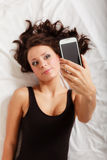 Sexy lazy girl lying with phone on bed in bedroom Royalty Free Stock Photos