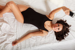 Sexy lazy girl lying with phone on bed in bedroom Stock Image