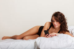 Sexy lazy girl lying with phone on bed in bedroom Royalty Free Stock Image