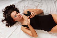 Sexy lazy girl lying with phone on bed in bedroom Stock Photo