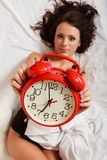 Sexy lazy girl lying with red alarm clock on bed Royalty Free Stock Photos