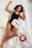 Sexy lazy girl lying with red alarm clock on bed Stock Photography