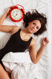 Sexy lazy girl lying with red alarm clock on bed Royalty Free Stock Images
