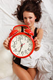 Sexy lazy girl lying with red alarm clock on bed Royalty Free Stock Photography