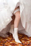 A sexy leg of the bride in a boot. A sexy leg of the bride with garter in a boot Stock Images