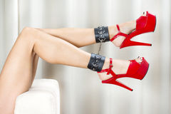 Sexy legs with ankle cuffs and red platform shoes. Female lages with black ankle cuffs and red fetish high heels with platform Stock Photo