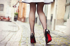 Legs in black high heel shoes. On stone pavement road in old city royalty free stock photography
