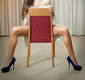 Sexy legs in black high heels on chair in hotel Royalty Free Stock Photos