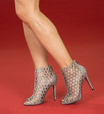Sexy legs in fancy high heels on the red carpet. Sexy legs of a woman wearing high heels ankle boots in silver metallic design on a red carpet Stock Images