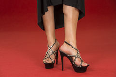 Sexy legs in fancy high heels on the red carpet. Sexy legs of a woman wearing a black dress and black high heels shoes with rhinestone decoration on a red carpet Royalty Free Stock Images