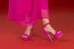 Sexy legs in fancy high heels on the red carpet. Sexy legs of a woman wearing a pink long dress and pink high heels shoes on a red carpet Royalty Free Stock Images