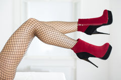 Sexy legs with fishnet stockings and ankle boots. Long and sexy female legs with fishnet stockings and  ankle boots platform shoes Royalty Free Stock Photo