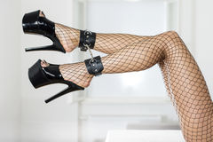 legs with fishnet stockings, ankle cuffs and platform shoes