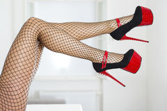 Sexy legs with fishnet stockings and extreme platform shoes. Long and sexy female legs with fishnet stockings and  extreme platform shoes with platform sole Royalty Free Stock Photography