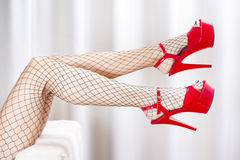 Sexy legs in fishnet stockings and red platform shoes Stock Photos