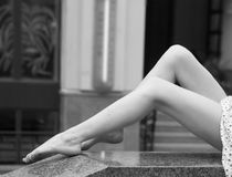 Sexy legs of girl on marble parapet. Black and white. Royalty Free Stock Image