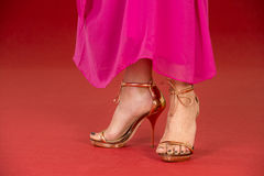 Sexy legs in gold high heels on the red carpet. Sexy legs of a woman wearing golden high heels and a long pink dress on a red carpet Royalty Free Stock Photo