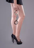 Sexy legs with handcuffs Royalty Free Stock Photography