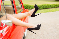 Sexy legs hanging out from car's window Stock Photo