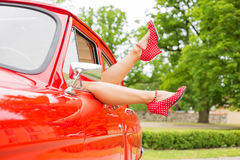 Sexy legs hanging out of red retro car Stock Image