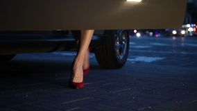 legs in heels getting into car at night stock footage