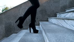 legs with high black heels climbs stairs of city. Business woman walking on boulvard alone. Attractive girl in stock video footage