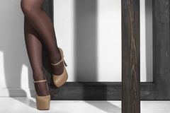Sexy legs in high heels near the pole. Sexy legs in black stockings and high heels near the pole, studio shot Stock Images