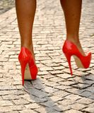 Legs with high heels shoes. Isolated on cubic stone stock image