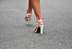 Sexy legs in high heels walking. Woman's legs in white high heels walking on the street Royalty Free Stock Image