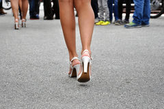 Legs in high heels walking. Woman's legs in white high heels walking on the street royalty free stock images