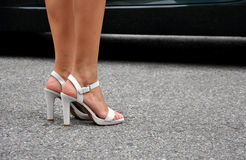 Sexy legs in high heels. Woman's legs in white high heels on the street Stock Images