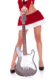 Legs of a santa woman with guitar. Legs of a santa woman holding an electric guitar, over white background stock images