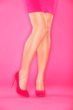 Sexy legs and shoes. Woman leg and pink high heels closeup on pink background Royalty Free Stock Image