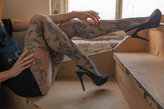 Sexy Legs In Stairwell. An image of a young woman's long legs in patterned tights and high heels Royalty Free Stock Photos