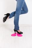 Sexy legs trampling on pink paper heart Stock Image