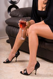 Sexy legs and wine. Close up of a woman in a short black dress sitting on a black leather sofa, holding a glass of wine Stock Photo