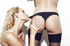 Sexy lesbian blonde woman bite lovers panties Royalty Free Stock Photography