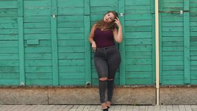 Portrait of a young girl with overweight in Park. Liberated girl with excess weight is leaning on a green fence, she is dressed in torn jeans and a t-shirt stock footage