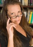 Sexy Librarian with Eyeglasses. Portrait of a professional woman peering sternly over eyeglasses or spectacles Royalty Free Stock Images